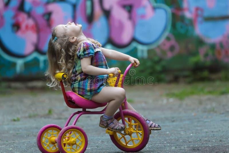 Девушка Preschooler нося проверенную тунику ехать желтый и розовый трицикл стоковое фото rf