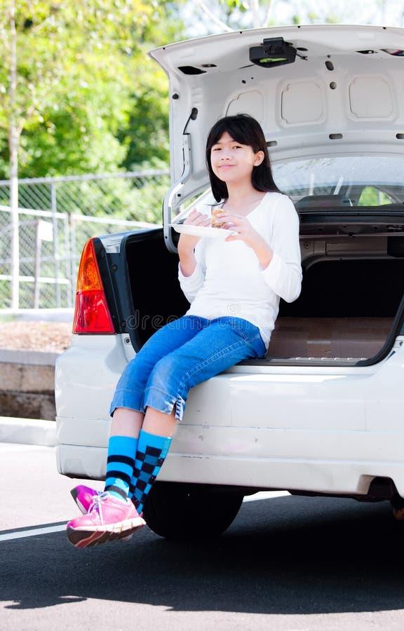 Девушка Preteen сидя на заднем бампере автомобиля есть обед стоковое фото rf
