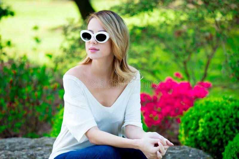 Девушка Redhead в белых солнечных очках приближает к цветкам стоковые фото