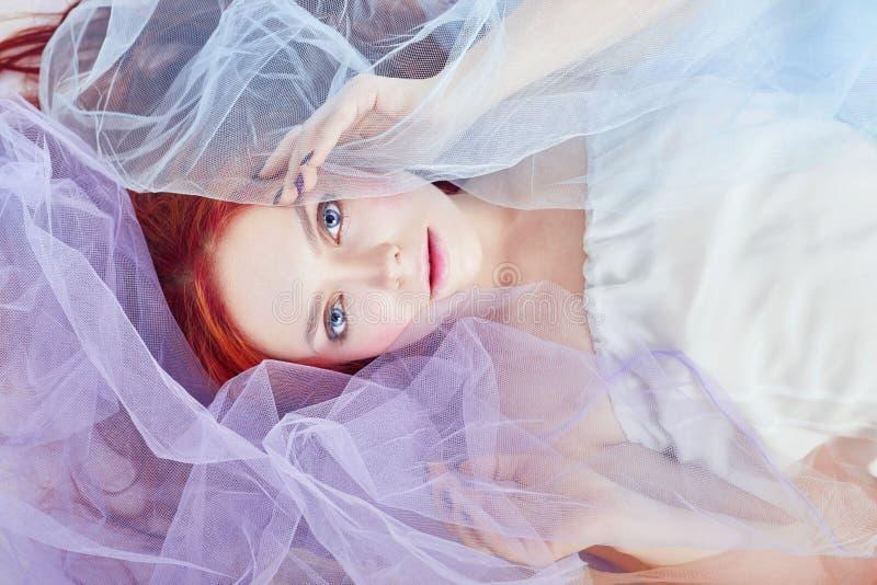 Девушка Redhead в платье светлого воздуха покрашенном лежит на поле, конце-вверх портрета Романтичная женщина с длинными волосами стоковое изображение