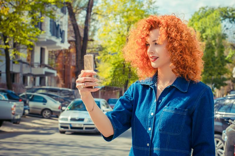 Девушка Redhead делая selfie используя смартфон и усмехаться стоковые фотографии rf