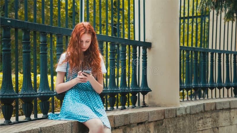Девушка redhead имбиря смотрит в телефон стоковые фотографии rf