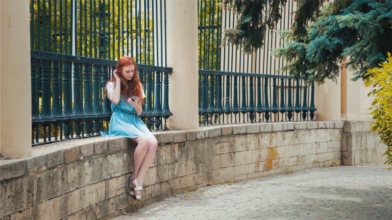 Девушка redhead имбиря смотрит в телефон стоковое изображение rf