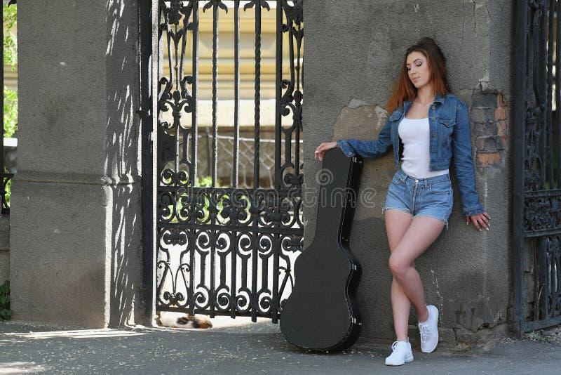 Девушка Redhead красивая в улице с гитарой в случае стоковые фото