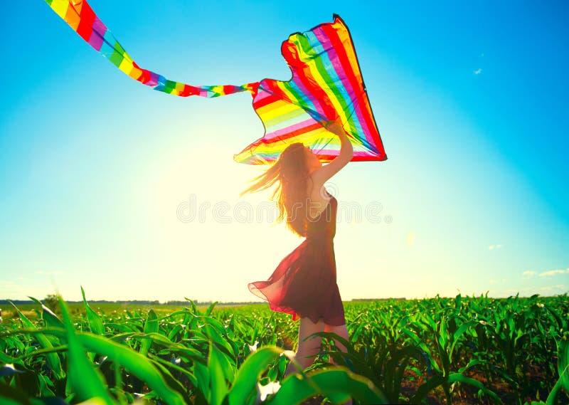 Девушка redhead красоты с летать красочный змей стоковое изображение rf
