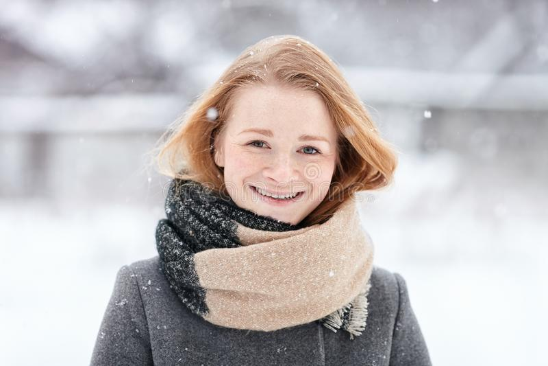Девушка redhead портрета красоты естественная смотря молодая прелестная нося связанное пальто шарфа серое на запачканной предпосы стоковая фотография