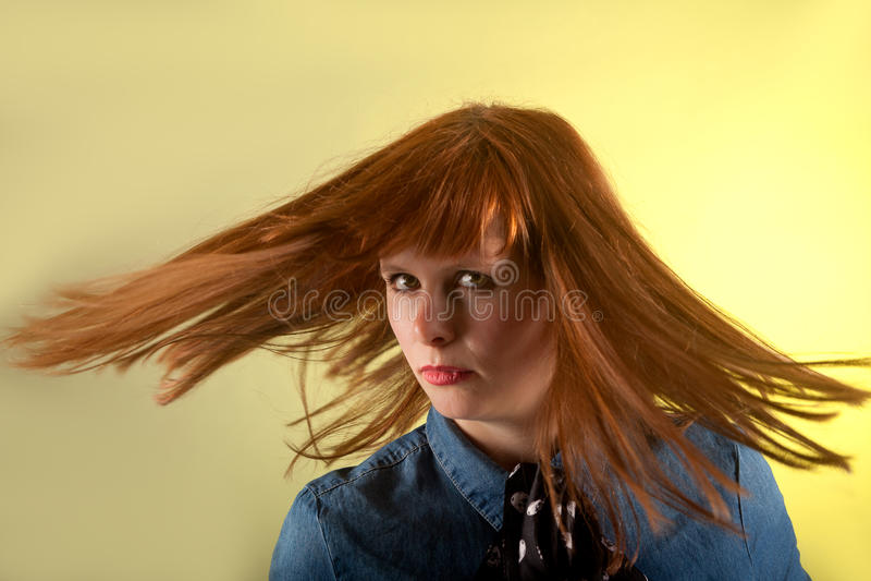 Девушка Redhead смотря подозрительную желтую предпосылку стоковое изображение rf