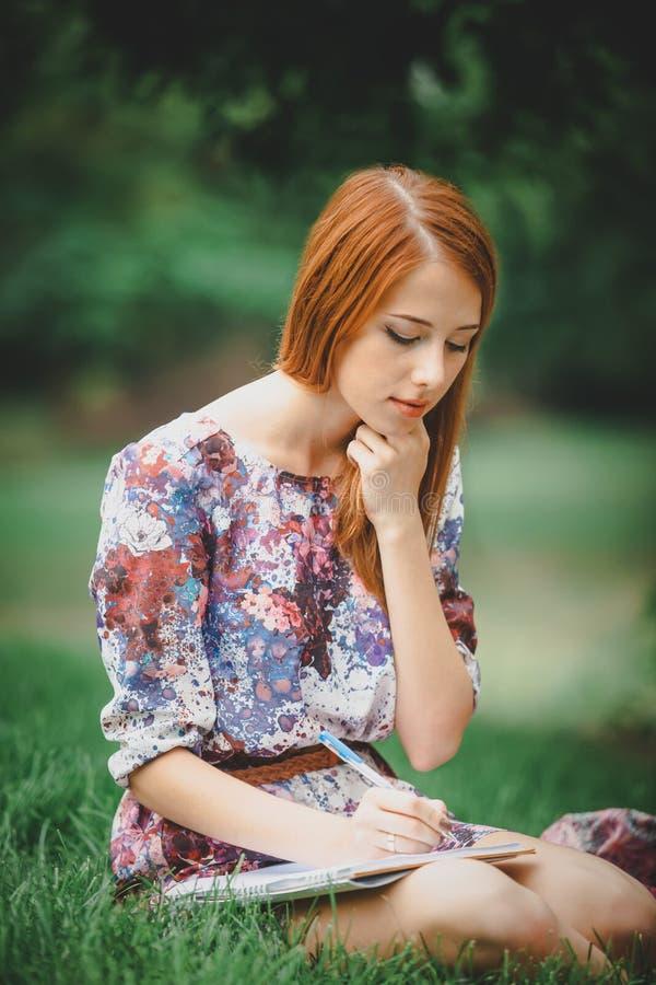 Девушка Redhead с тетрадью на зеленой лужайке стоковые изображения