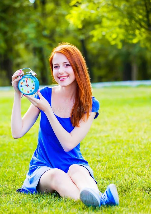Девушка Redhead с часами в парке стоковая фотография rf