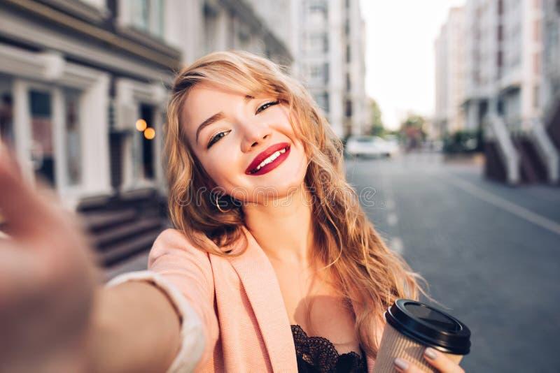 Девушка selfie-портрета крупного плана милая белокурая на улице в городе Она имеет vinous губы, усмехаясь к камере стоковое изображение rf