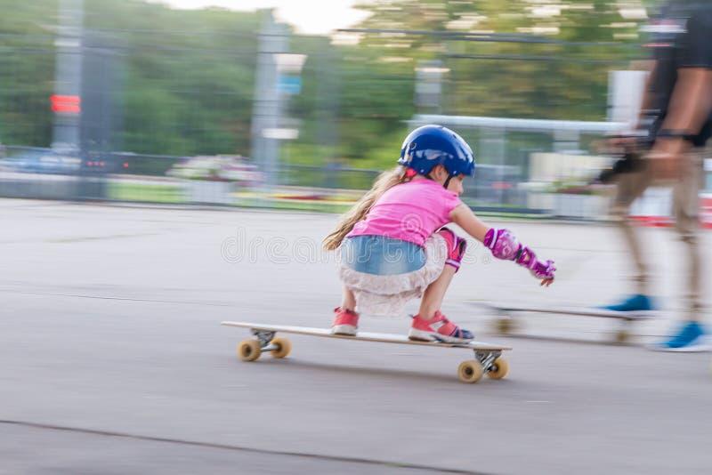 Девушка skateboarding на естественной предпосылке стоковая фотография
