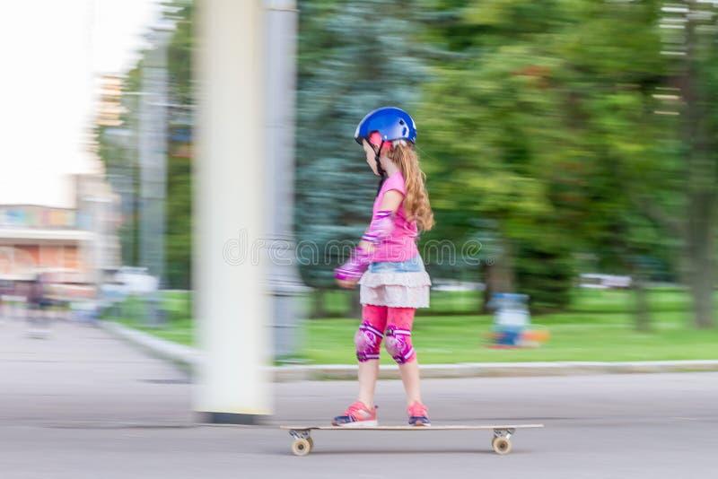 Девушка skateboarding на естественной предпосылке стоковые изображения