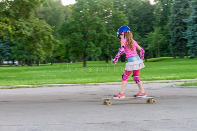 Девушка skateboarding на естественной предпосылке стоковое изображение