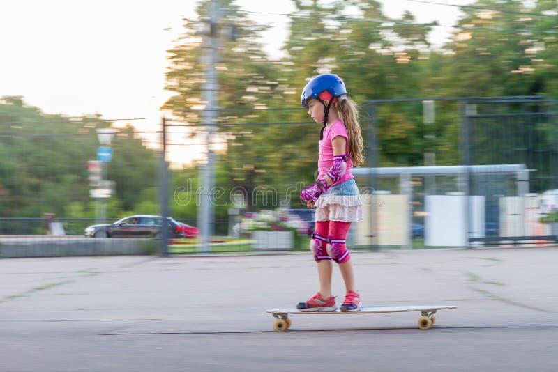 Девушка skateboarding на естественной предпосылке стоковое фото