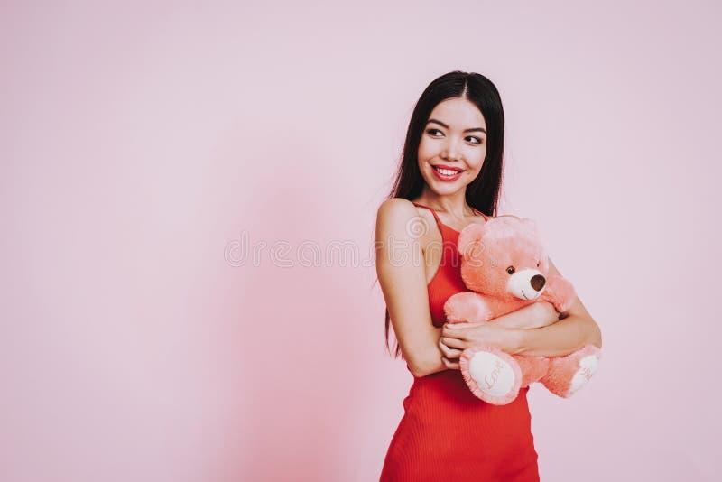 Девушка Smilling с медведем Taddy на розовой предпосылке стоковые фотографии rf