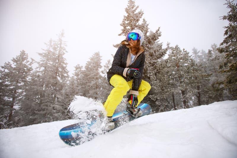 Девушка Snowboarder в действии на осуществляемом лыж стоковые изображения