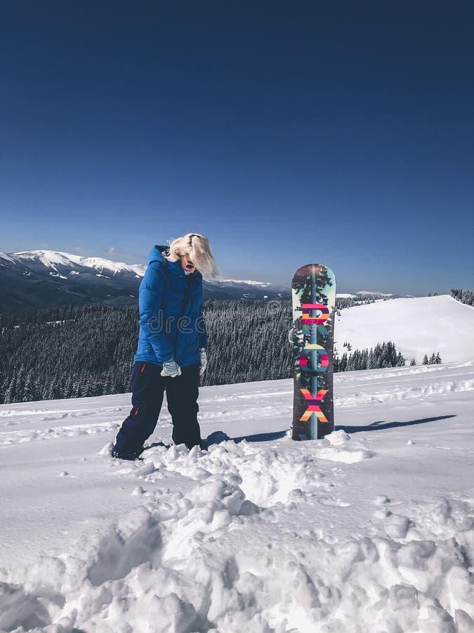 Девушка Snowboarder красивая белокурая в синем пиджаке при ее доска стоя в снеге в горах стоковое фото rf