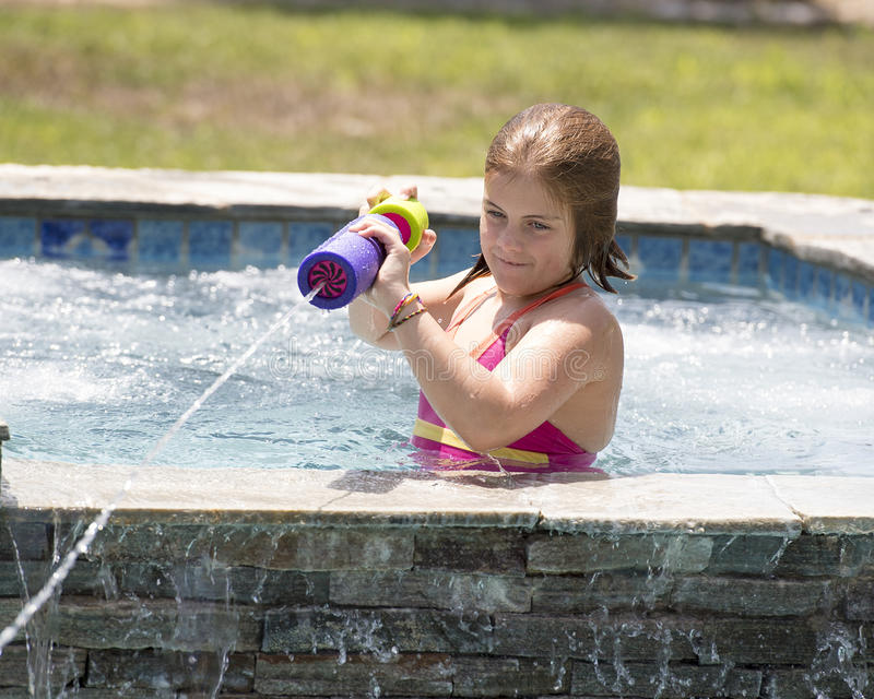 Девушка squirting вода от бассейна стоковое фото