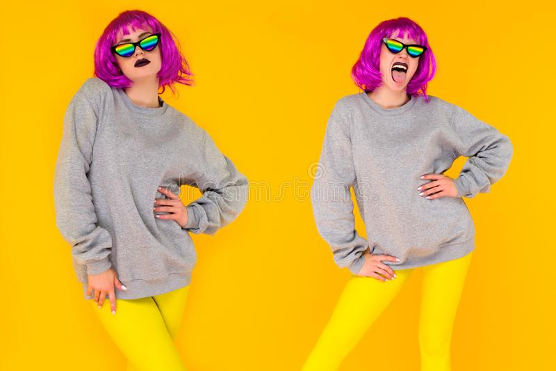 Девушка Wo лесбосская в розовых солнечных очках парика и радуги представляя на желтой предпосылке стоковые изображения