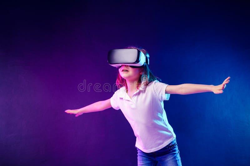 Девушка 7 y O испытывать игру шлемофона VR на красочной предпосылке Ребенок используя устройство игры для виртуальной реальности стоковая фотография