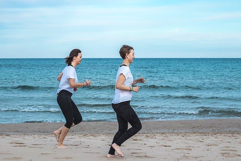 Девушки бежать вокруг пляжа стоковые фотографии rf