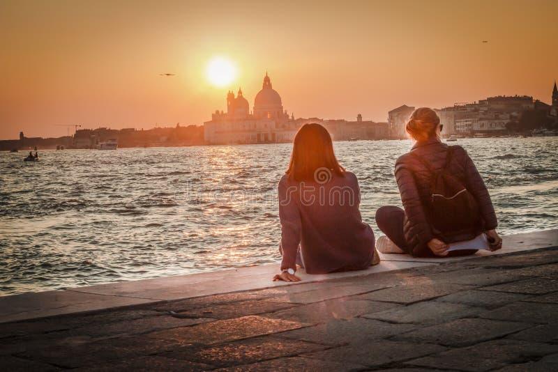 2 девушки восхищают сценарный заход солнца над салютом della Santa Maria в Венеции стоковое фото