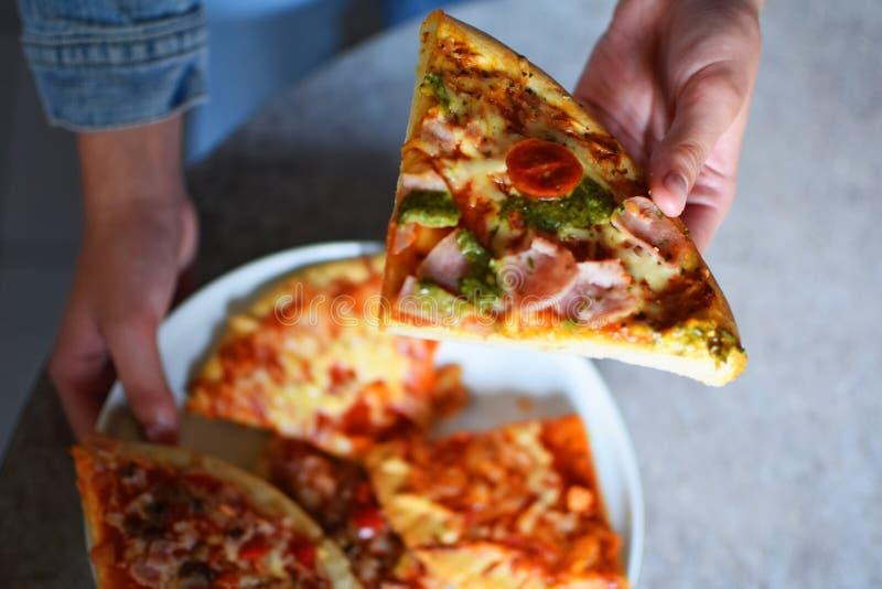 Девушки вручают держать часть пиццы стоковые фото