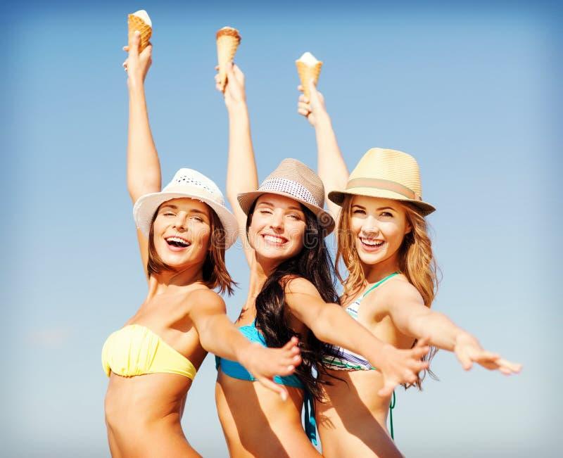 Девушки в бикини с мороженым на пляже стоковая фотография rf