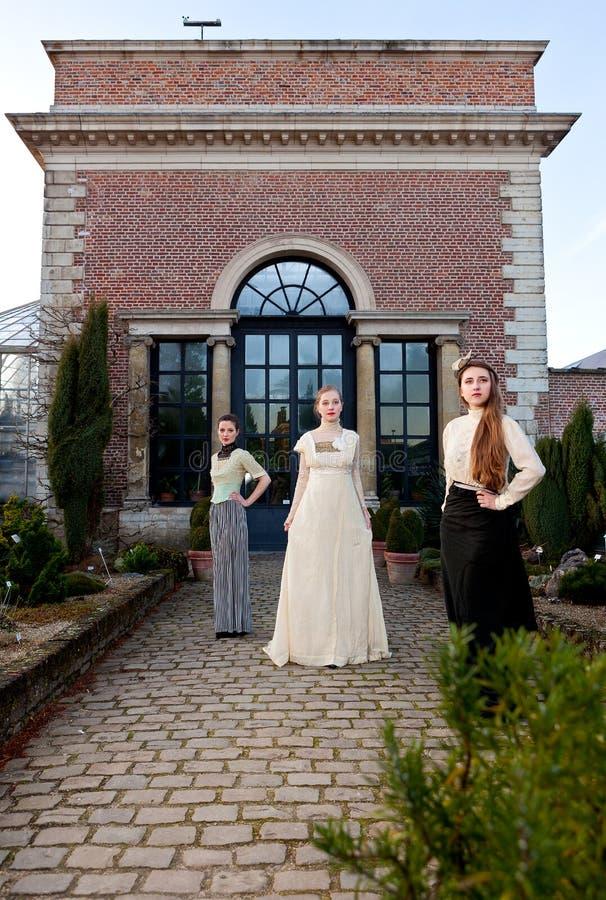 Девушки в викторианец перед старым домом стоковая фотография rf