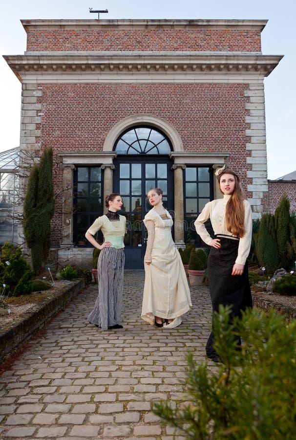 Девушки в викторианец перед старым домом стоковое фото rf