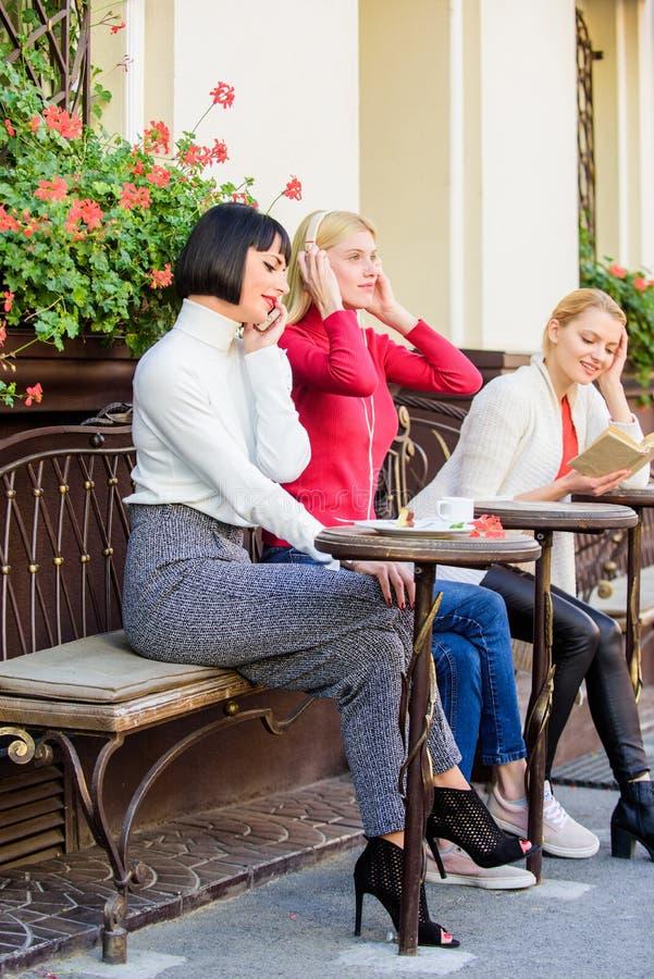 Девушки в кафе социальное разнообразие слушая музыка книга чтения говорить по телефону Frienship трата свободного времени ослабьт стоковые фото