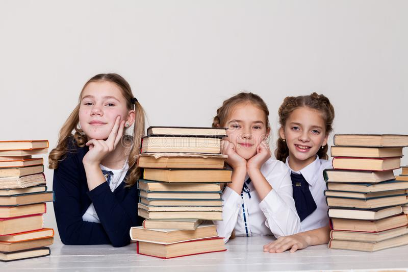 3 девушки в классе изучая много книг стоковые изображения
