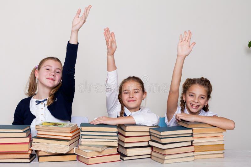 3 девушки в классе, подняли руку до ответа стоковые изображения rf