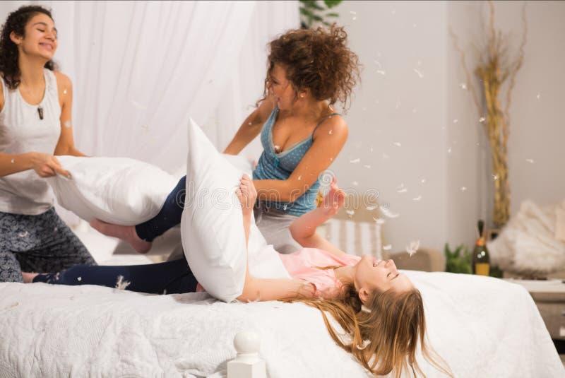 Девушки в кровати имея бой подушками в пижамах на девичнике в спальне стоковое фото