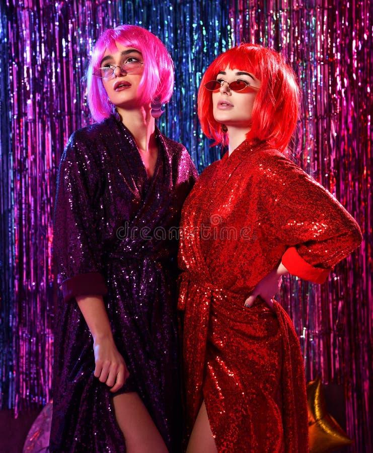 Девушки в париках и стильные блестящие платья с sequins, в неоновом свете диско Отпразднуйте, имейте потеху, отпразднуйте что-то стоковые изображения rf