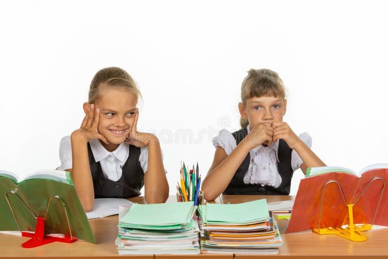 Девушки в различных эмоциях думают о том, что-то пока сидящ на столе в школе стоковые фотографии rf