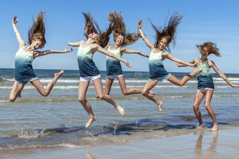 Девушки группы скача на пляж стоковое фото
