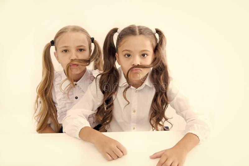 Девушки делают усик с предпосылкой длинных волос белой Концепция стиля причесок Школьницы имея потеху со стилем причесок усика стоковые изображения rf