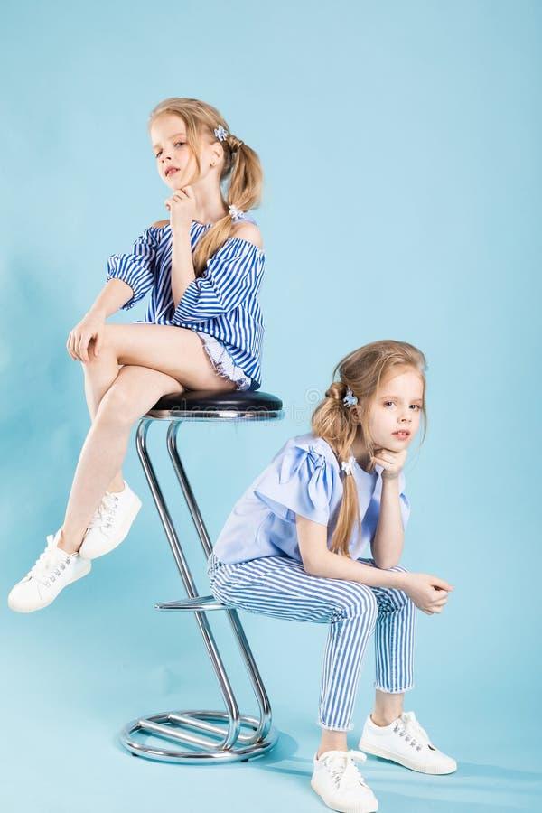 Девушки дублируют в свете - голубые одежды представляют около барного стула на голубой предпосылке стоковые фотографии rf
