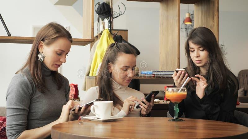 3 девушки женщин в кафе просматривают их мобильные телефоны Дружелюбная встреча в кафе стоковые изображения rf