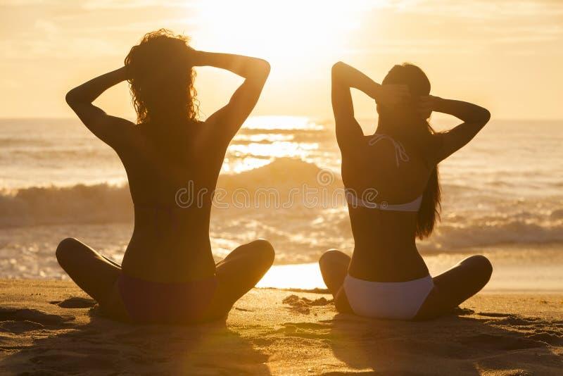 Девушки женщин сидя пляж бикини захода солнца восхода солнца стоковые изображения