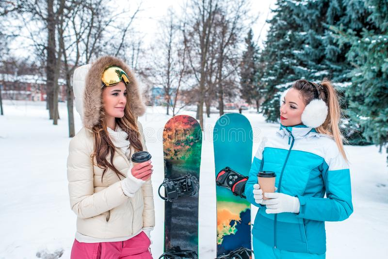 2 девушки женщин, девушки спорт, в зиме на предпосылке снега и елей Они говорят в их руках с стоковое изображение