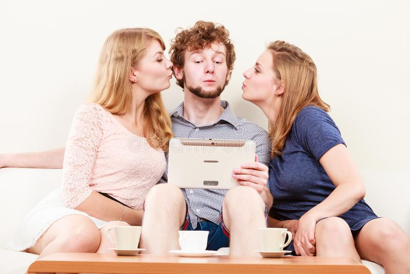 Девушки женщин целуя парня человека с планшетом Потеха стоковые изображения
