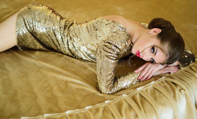 Девушки золота моды Шикарная молодая женщина в платье золота в кровати Сексуальная и красивая женщина в кровати Сексуальная девуш стоковое фото