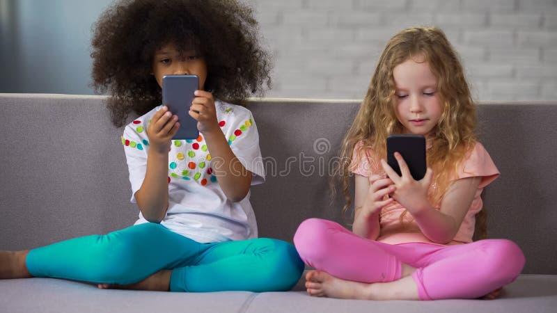 2 девушки играя игры на смартфонах вместо играя совместно наркоманию устройства стоковое изображение