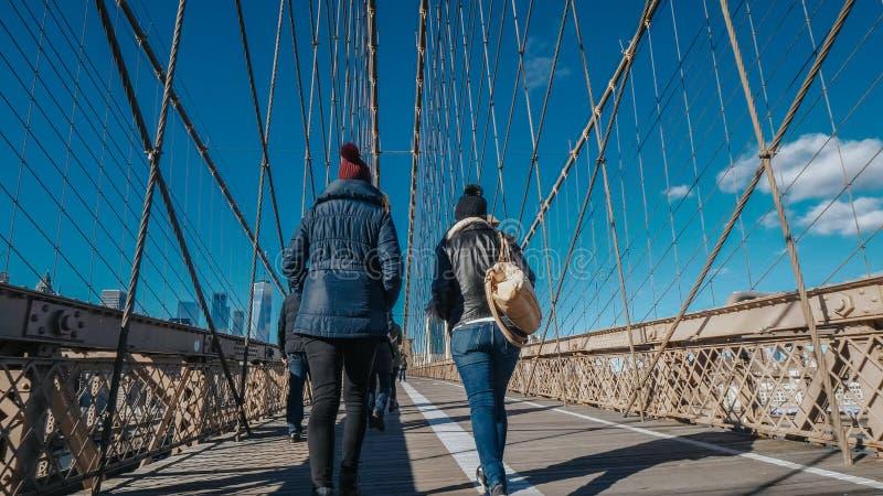 2 девушки идут над известным Бруклинским мостом в Нью-Йорке стоковое изображение