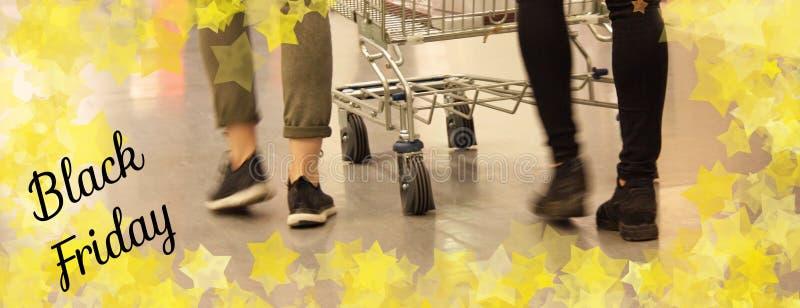 Девушки идут ходить по магазинам с вагонеткой покупок стоковые фотографии rf