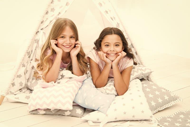 Девушки имея дом типи потехи Girlish отдых Сплетни доли сестер имея потеху дома Партия пижам для детей Уютный стоковое фото rf