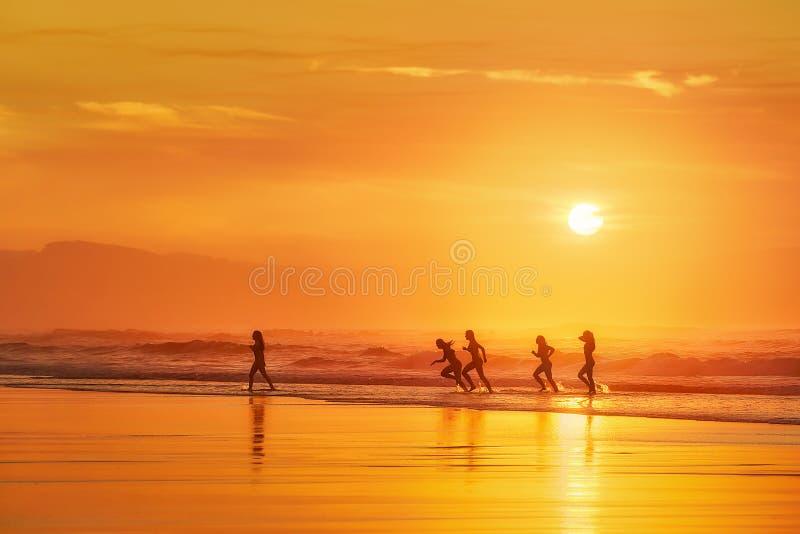Девушки имея потеху в пляже на заходе солнца стоковое фото rf