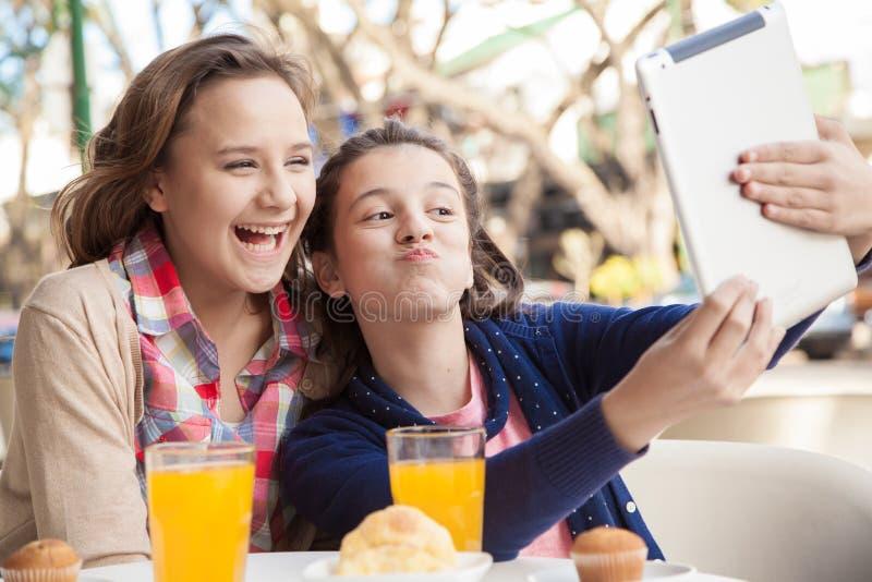 Девушки используя таблетку в улице стоковая фотография